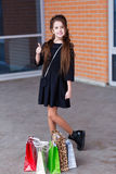 Beautiful young girl with a lot of packages at the outlet of the Royalty Free Stock Photos