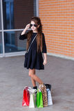 Beautiful young girl with a lot of packages at the outlet of the Royalty Free Stock Images