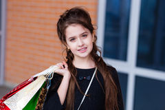 Beautiful young girl with a lot of packages at the outlet of the Stock Photography