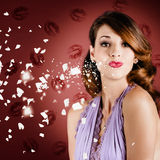Beautiful young girl in love blowing lipstick kiss. Lovely romantic pin-up girl blowing a valentine kiss with magical style while heart shape paper pieces float Royalty Free Stock Images