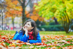 Beautiful young girl in the Luxembourg garden of Paris. Beautiful young tourist in Paris on a fall day, laying on the ground in the Luxembourg garden with stock image