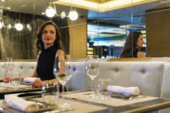 Beautiful young girl in luxury restaurant interior Royalty Free Stock Photos