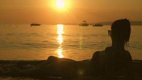 Beautiful young girl lying on the beach at sunset. Girl on vacation relaxing on the beach and looking at sunset. Summer. Vacation. Holiday travel stock video footage