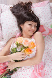Beautiful young girl lying in bed with bouquet of roses Stock Image
