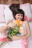 Beautiful young girl lying in bed with flowers Royalty Free Stock Photography