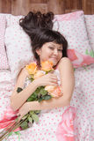 Beautiful young girl lying in bed, glad bestowed colors Stock Image