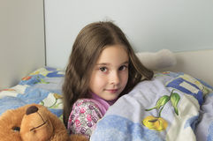 Beautiful young girl lying in bed. Portrait of a beautiful young girl lying in bed Stock Photo