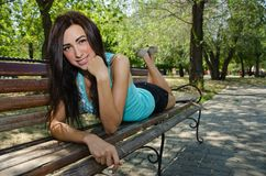 Beautiful young girl lying on a bench in the park and smiling Royalty Free Stock Images