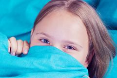 Beautiful young girl lying down in the bed and sleeping. Teen girl with open eyes covers her face with blue blanket in the morning royalty free stock photography