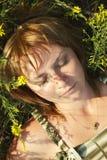 Beautiful young girl lying on grass Stock Image