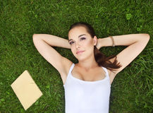 Beautiful young girl lying on the grass Stock Photos