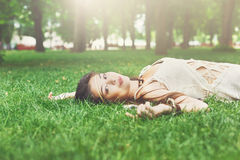 Beautiful young girl lying on grass in summer park Royalty Free Stock Photography