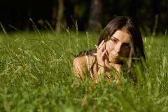 Beautiful young girl lying in green grass Stock Photos