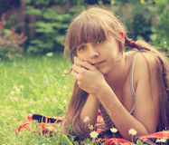 Beautiful Young Girl Lying on Green Grass outdoor. Stock Photo