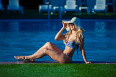 A beautiful young girl is lying on the ledge of the pool. She is wearing a pretty swimsuit, sunglasses and hat. She is Stock Images