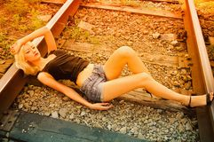 Beautiful young girl lying on rails Stock Photography