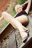 Beautiful young girl lying on rails Stock Images
