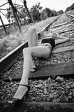 Beautiful young girl lying on rails Royalty Free Stock Image