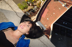 Beautiful young girl lying on the roof Stock Images