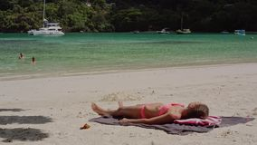 Beautiful young girl lying on the sand on the beach sunbathes, on a summer sunny day. Beautiful young girl lying on the sand on the beach sunbathes, on a sunny stock video