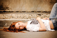Beautiful young girl lying on the street Royalty Free Stock Image