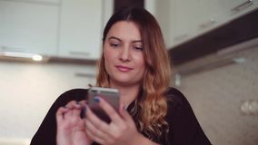 A beautiful young girl makes a call to her friend using a smartphone. Home style. Beautiful young girl with long hair is making a call to her friend using a stock video footage