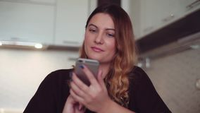 Beautiful young girl makes a call to her girlfriend using a smartphone and smiles. Beautiful young girl with long hair is making a call to her friend using a stock video footage