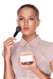 A beautiful young girl with makeup brush Stock Photography