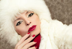 Beautiful young girl. A beautiful young girl with makeup and red nail Polish in a white fur winter hat royalty free stock photography