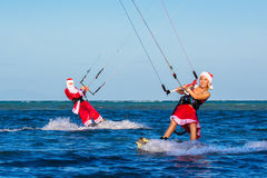 Beautiful young girl and man on the kites in the costume of Santa Claus. Christmas and New year on a tropical island. Extreme stock photo