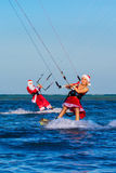 Beautiful young girl and man on the kites in the costume of Santa Claus. Christmas and New year on a tropical island. Extreme royalty free stock photo