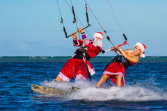 Beautiful young girl and man on the kites in the costume of Santa Claus. Christmas and New year on a tropical island. Extreme. Beautiful young girl and men on stock photos