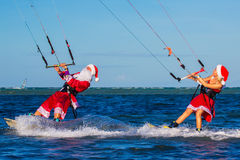Beautiful young girl and man on the kites in the costume of Santa Claus. Christmas and New year on a tropical island. Extreme stock photography