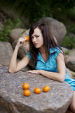 Beautiful young girl with the mandarins in nature Royalty Free Stock Photo