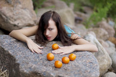 Beautiful young girl with the mandarins in nature Stock Image