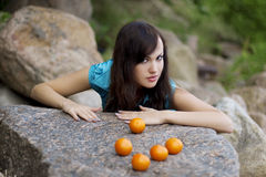 Beautiful young girl with the mandarins in nature Stock Photography