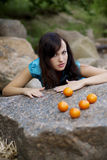 Beautiful young girl with the mandarins in nature Stock Images