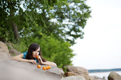 Beautiful young girl with the mandarins in nature Royalty Free Stock Photography