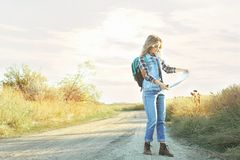 Beautiful young girl with map on countryside road royalty free stock photo
