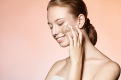 Beautiful young girl massages the face scrub and smiles Royalty Free Stock Images