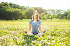 Beautiful young girl meditating in autumn park Stock Photo