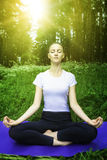 Beautiful young girl meditating in the forest Royalty Free Stock Photography