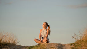 Beautiful young girl meditating on the hill in the rays of the setting sun Royalty Free Stock Photography