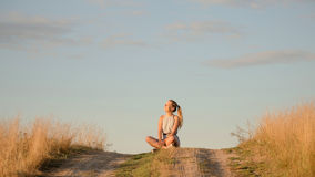 Beautiful young girl meditating on the hill in the rays of the setting sun Royalty Free Stock Images