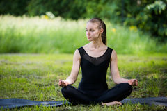 Beautiful young girl meditating in summer park Stock Photos