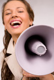 Beautiful young girl with megaphone over white Royalty Free Stock Images