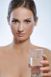 Beautiful young girl with mineral water in gla Royalty Free Stock Photos