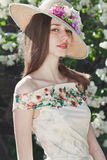 Beautiful young girl model posing near blooming lilacs at spring Royalty Free Stock Image