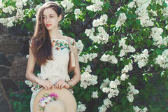 Beautiful young girl model posing near blooming lilacs at spring Royalty Free Stock Images