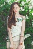 Beautiful young girl model posing near blooming lilacs at spring Royalty Free Stock Photos
